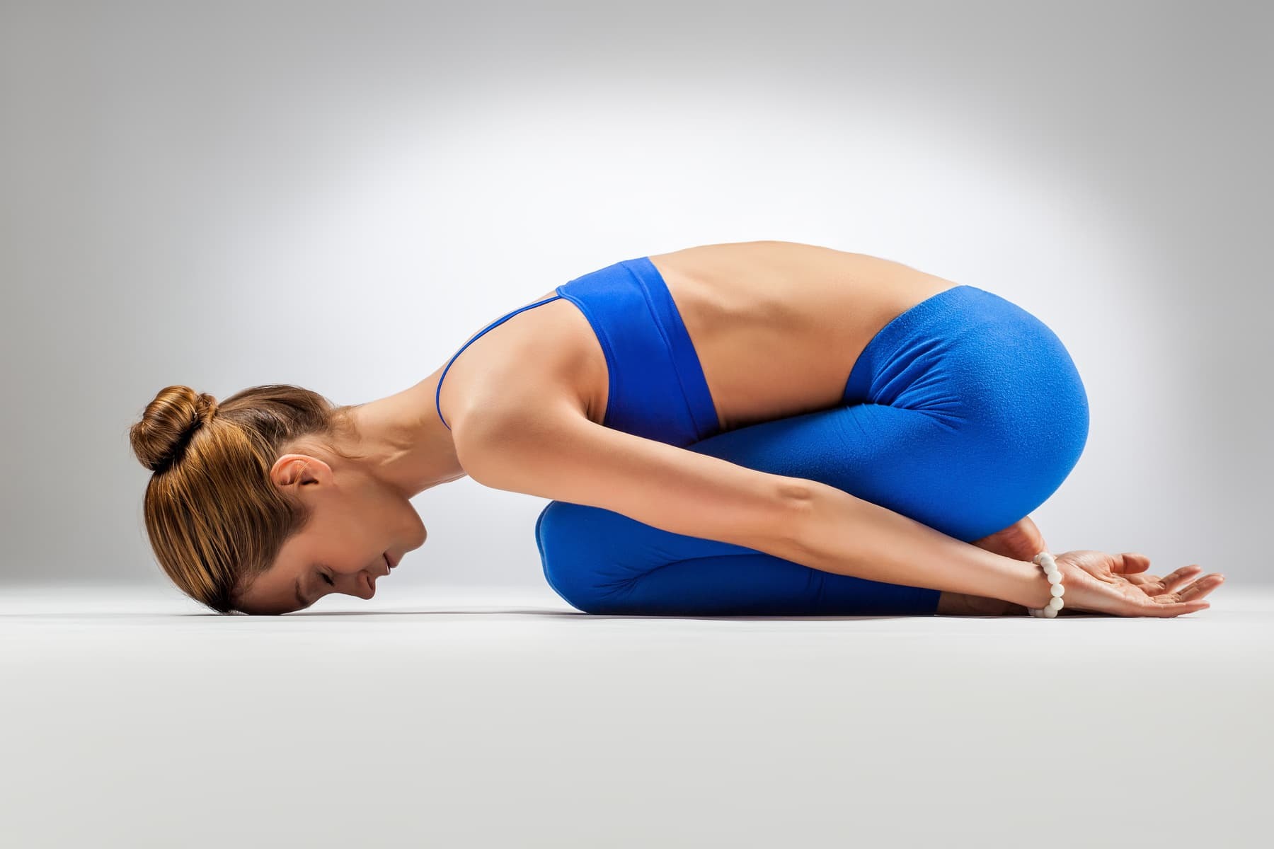 young beautiful yoga posing balasana on a gray studio background